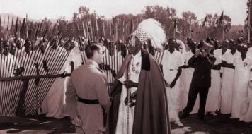 Um colonialista belga com o povo ruandês; a separação étnica imposta pelos colonos culminou numa divisão política entre as duas tribos (Reprodução)