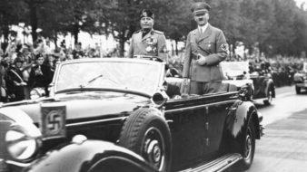 Benito Mussolini, símbolo do fascismo, e Adolf Hitler, símbolo do nazismo, passeiam de carro por Berlim. A população os festeja nas ruas.