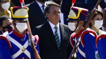 Bolsonaro está cercado de soldados vestidos de azul e acompanhado de sua esposa para o desfile do dia da independência.