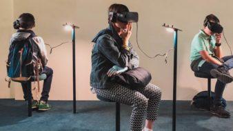 três crianças estão sentadas em uma sala bege. Elas utilizam óculos de realidade virtual.