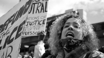 Mulher branca em protetos contra o racismo nos Estados Unidos, com pautas de identidade