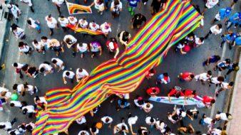 Manifestação LGBTQ+ representa a união pela identidade. Bandeira do arco-íris ao centro. Várias pessoas