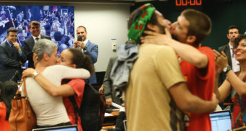 Jair Bolsonaro, entre os deputados Marco Feliciano e Eduardo Bolsonaro, observa beijaço na Câmara dos Deputados